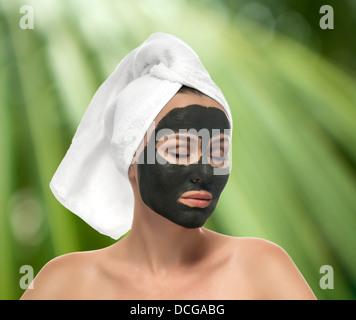La donna riceve una maschera di fango sullo sfondo verde Foto Stock