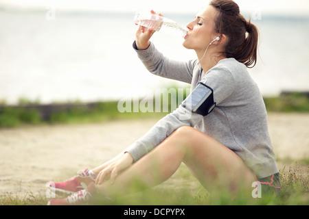 Stanchi del pareggiatore femmina seduto sull'erba e di bere acqua in bottiglia Foto Stock