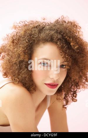 Ritratto di giovane donna con capelli ricci Foto Stock