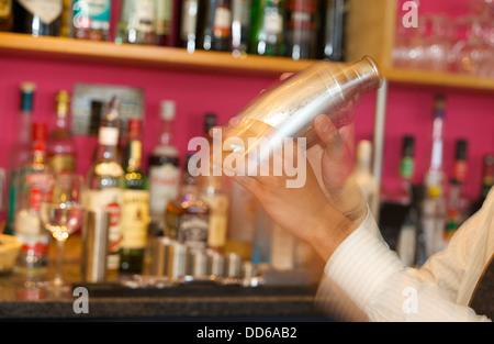 Shaker essendo agitata in una barra di colore rosa Foto Stock