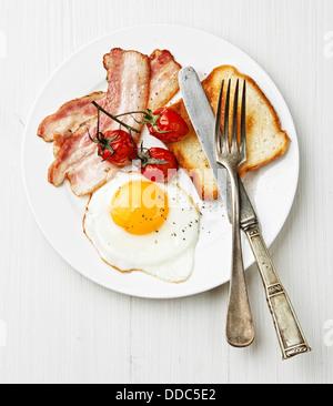 La prima colazione con uova fritte e pancetta sulla piastra Foto Stock