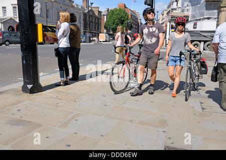 Londra, Inghilterra, Regno Unito. Coppia giovane spingendo le biciclette sul marciapiede in Whitehall Foto Stock