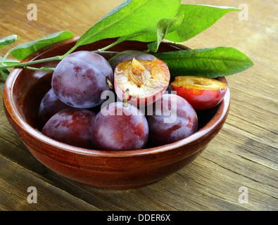 Mature prugne viola su una tavola di legno Foto Stock