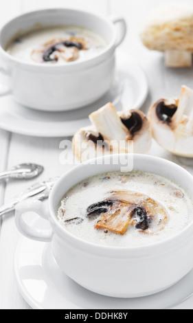 Bianco crema zuppa di funghi servita in due ciotole bianco Foto Stock