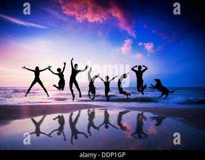 Le persone felici e cane jumping insieme sulla spiaggia al tramonto