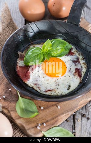 Uovo fritto in una piccola padella su vintage sfondo di legno Foto Stock