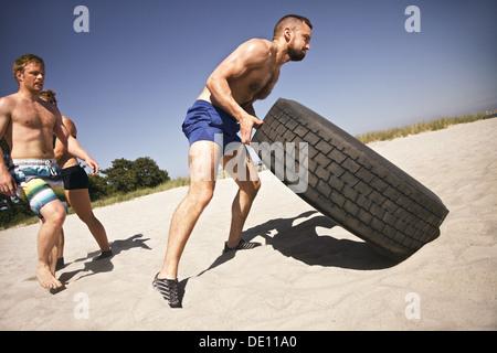 Tenace atleta maschio capovolgimento di un carrello pneumatico. I giovani facendo esercizio crossfit sulla spiaggia. Foto Stock