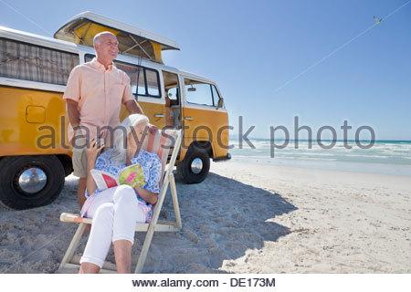 Coppia senior rilassante al di fuori van di sunny beach Foto Stock