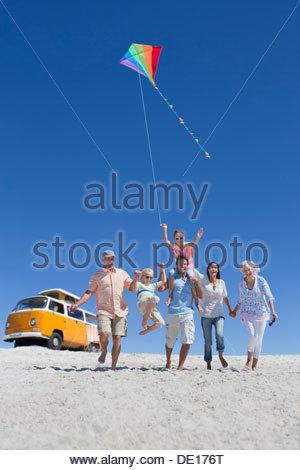 Felice multi-generazione famiglia con kite camminando sulla spiaggia soleggiata con van in background Foto Stock