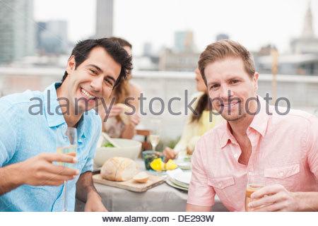 Ridere gli amici a bere champagne a parte esterna Foto Stock