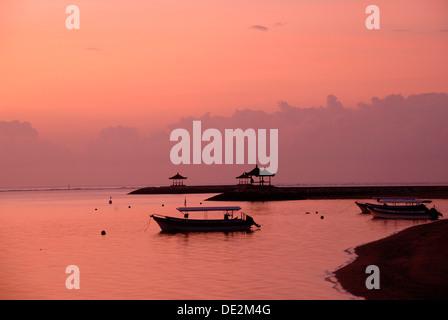 Di colore rosa sunrise, barche in silhouette, spiaggia di Sanur, Bali, Indonesia, Asia sud-orientale, Asia Foto Stock