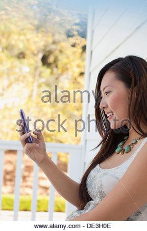 Donna sorridente con telefono cellulare all'aperto Foto Stock