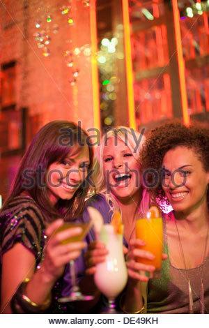Gli amici a bere un cocktail in discoteca Foto Stock