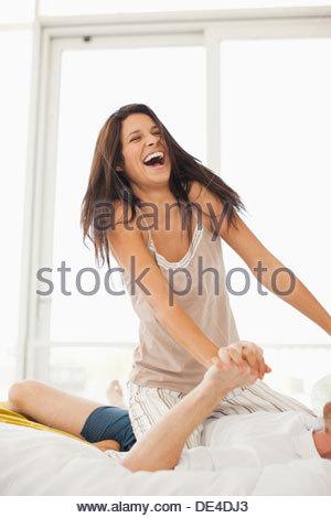 Coppia sorridente in pigiama giocando a letto Foto Stock