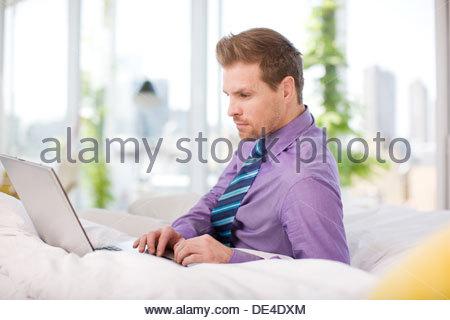 Imprenditore che stabilisce nel letto digitando su laptop Foto Stock