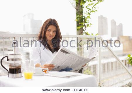 Donna che legge il giornale e avente la colazione sul balcone Foto Stock