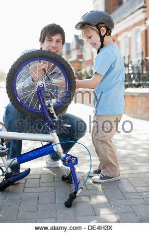 Padre e figlio di fissaggio pneumatico per bicicletta sul marciapiede Foto Stock
