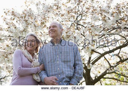 Coppia senior abbracciando sotto alberi in fiore Foto Stock