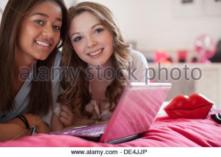 Sorridente ragazze adolescenti utilizzando laptop insieme Foto Stock