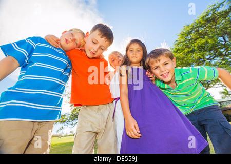 Gruppo di felici i bambini che giocano insieme al di fuori, il concetto di amicizia Foto Stock