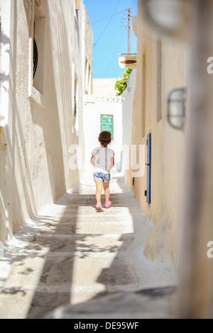 Vista posteriore di adorabile ragazza camminare da solo in strade strette a villaggio Emporio sull'isola di Santorini, Foto Stock