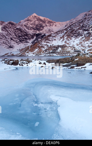 Prima luce su Mount Snowdon oltre congelati Llyn Llydaw, Snowdonia National Park, North Wales, Regno Unito Foto Stock