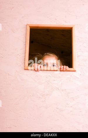 Ragazza 3 anni, guardando attraverso la finestra Foto Stock
