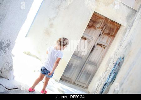 Adorabile ragazza camminare da solo in strade strette del villaggio Emporio sull'isola di Santorini, Grecia Foto Stock