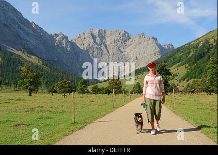 Donna escursionismo con una miniatura Schnauzer, Engalm, in fornt delle montagne Karwendel, Großer Ahornboden, Alpenpark Karwendel