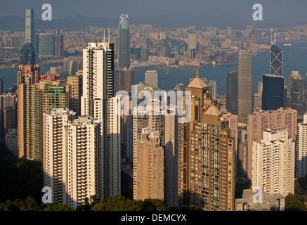 Vista attraverso i grattacieli nel quartiere centrale e il porto di Victoria a Kowloon, Hong Kong Foto Stock
