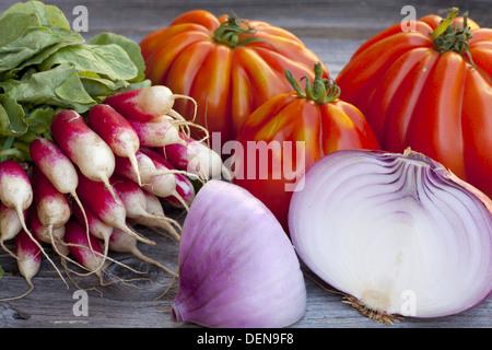 Coeur de boeuf Pomodori, grandi cipolle rosse e ravanelli freschi dal mercato settimanale su un vecchio tavolo in legno
