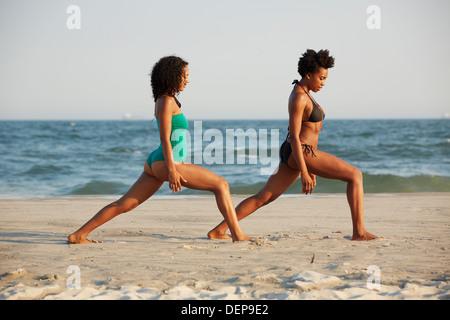 Le donne a praticare yoga sulla spiaggia Foto Stock