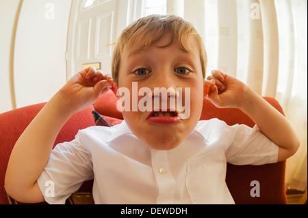 A dieci anni di vecchio ragazzo tirando una divertente volto al chiuso Foto Stock