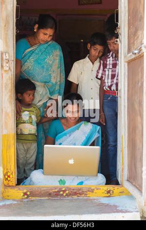 Rurale villaggio indiano donne e famiglie in cerca di un computer portatile Apple nella sua casa di porta. Andhra Pradesh, India
