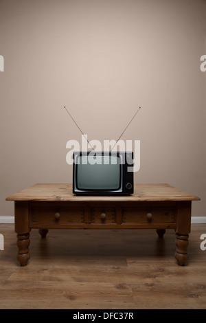Un vecchio televisore retrò su un tavolo con schermo vuoto in una stanza vuota Foto Stock