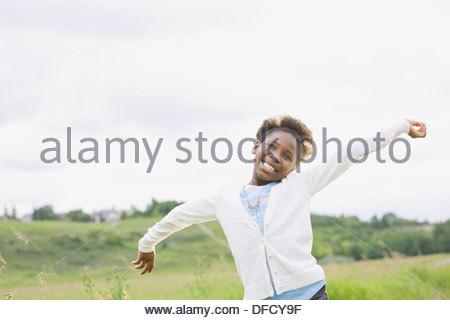 Ritratto di ragazza sorridente con le braccia aperte all'aperto Foto Stock