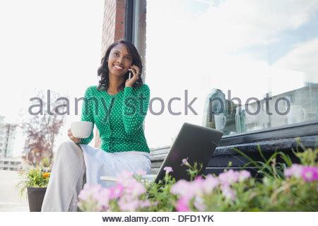 Proprietario femmina tramite telefono cellulare al di fuori cafe Foto Stock