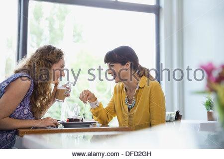 Amici di sesso femminile spettegolare in ristorante Foto Stock