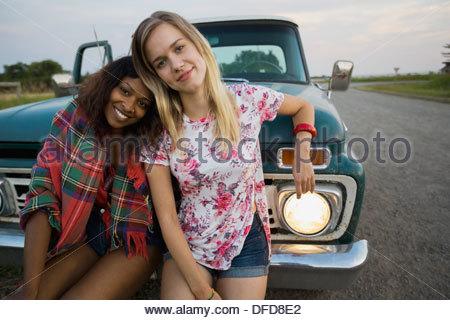 Ritratto di amici di sesso femminile appoggiata contro il pick-up Foto Stock