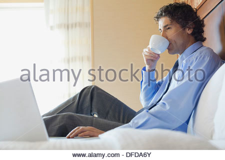 Imprenditore lavora su computer portatile mentre si beve il caffè in camera di albergo Foto Stock