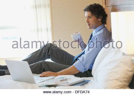 Imprenditore con tazza di caffè lavorando sul computer portatile in camera di albergo Foto Stock