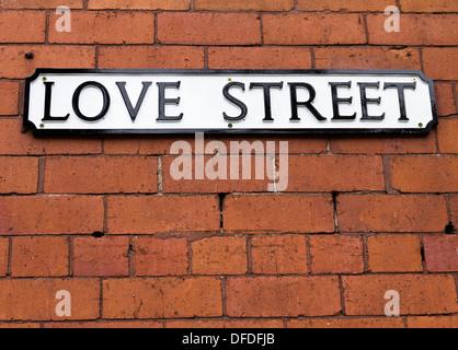 Amore strada segno su un rosso muro di mattoni Foto Stock
