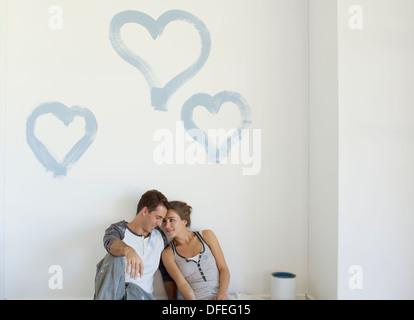 Giovane pittura cuori blu sulla parete Foto Stock