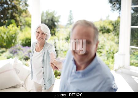 Coppia senior tenendo le mani sul patio Foto Stock