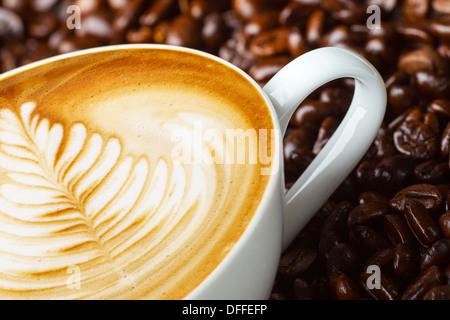 Latte Art, caffè in chicchi di caffè sfondo Foto Stock
