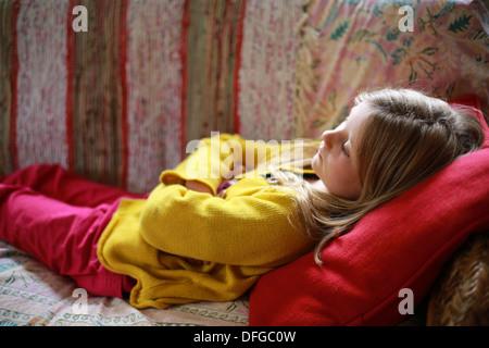 Giovane ragazza distesa su un divano Foto Stock