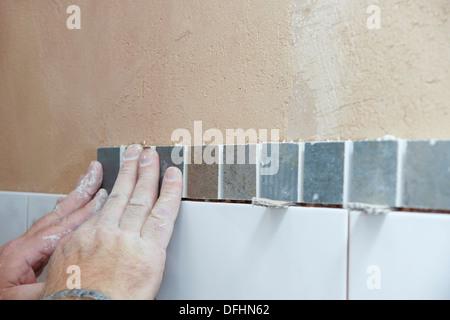 Installatore di attaccare le piastrelle in una camera umida
