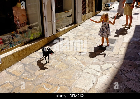 Ragazza guardando un cane in strada, Palma di Mallorca