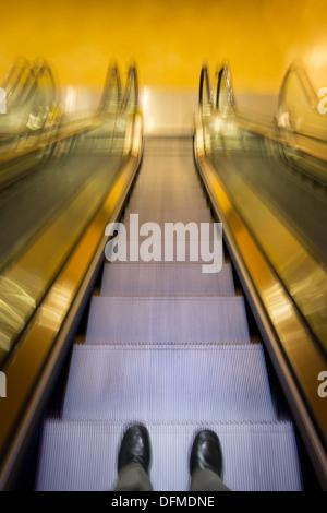 Imprenditore il piedi scendendo Escalator Foto Stock
