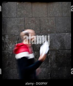 Sfocate sagome di persone che passano attraverso una parete Foto Stock